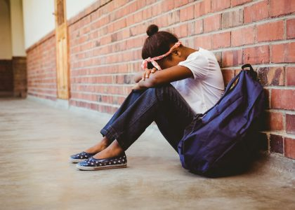 Tensed girl sitting against brick wall in school corridor