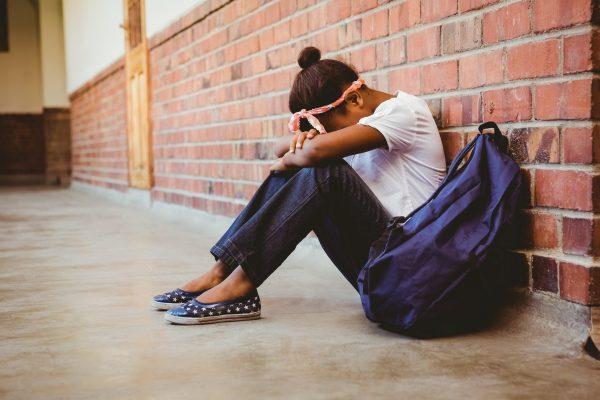 Tensed girl sitting against brick wall in school corridor